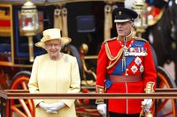 In this file photo on June 16, 2012, Britain's Queen Elizabeth II, and Prince Philip take a salute as the Guards march past outside Buckingham Palace after the Trooping The Color parade at Horse Guards Parade in London. (AP Photo/Sang Tan)