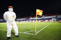 """A Conmebol worker stands guard on the pitch at the """"Defensores del Chaco"""" Stadium before the start of a Copa Libertadores soccer match between Brazil's Gremio and Ecuador's Independiente del Valle, in Asuncion, Paraguay, on April 9, 2021. (Natalia Aguilar/Pool via AP)"""
