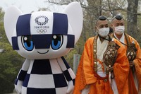 Tokyo 2020 Olympic Games mascot Miraitowa and Buddhist monks wearing protective face masks attend a ceremony to unveil a display of an Olympic Symbol on Mt. Takao in Hachioji, west of Tokyo, on April 14, 2021, to mark 100 days before the start of the Olympic Games. (Kim Kyung-Hoon/Pool)