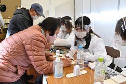 新型コロナウイルスワクチンの接種を受けるため受け付けをする高齢者(東京都八王子市で4月12日)