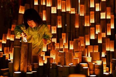 復興を願う竹灯籠に明かりをともす女の子=熊本県益城町で2021年4月14日午後7時27分、徳野仁子撮影