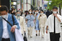 People wearing face masks to protect against the spread of the coronavirus walk on a street in Tokyo, on April 13, 2021. (AP Photo/Koji Sasahara)