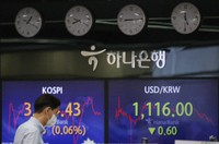 A currency trader walks by the screens showing the Korea Composite Stock Price Index (KOSPI), left, and the foreign exchange rate between U.S. dollar and South Korean won at the foreign exchange dealing room in Seoul, South Korea, on April 15, 2021. (AP Photo/Lee Jin-man)