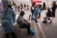 In this Feb. 10, 2021, file photo, Viola Roberson, 75, far right, and 61-year-old Mark McNamee, foreground, wait for their COVID-19 vaccine at a vaccination site set up in the parking lot of the Los Angeles Mission in the Skid Row area of Los Angeles.  (AP Photo/Jae C. Hong, File)