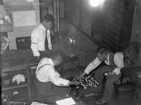 Newspaper journalists are seen playing Go at their local bureau during a break in their coverage of army exercises held in Hokkaido, in October 1936. (Mainichi)