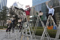 South Korean peace activists on the ladders stage a rally supporting Myanmar's democracy, outside the POSCO office in Seoul, South Korea on Feb. 22, 2021. (AP Photo/Ahn Young-joon)