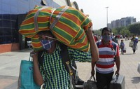 People wearing masks as a precaution against the coronavirus walk to board trains at Lokmanya Tilak Terminus in Mumbai, India, on April 16, 2021. (AP Photo/Rajanish Kakade)