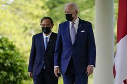 日米首脳共同記者会見に臨む菅義偉首相(左)とバイデン米大統領=ホワイトハウスで2021年4月16日、AP
