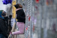 Nevaeh Gibson inspects a two-layer fenced perimeter around the Brooklyn Center Police Department during a protest in response to the shooting death of Daunte Wright, on April 15, 2021, in Brooklyn Center, Minn. (AP Photo/John Minchillo)