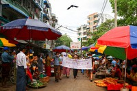 """Anti-coup protesters hold signs that read """"We Support NUG"""" that stands for 'national unity government' as they march on a street where vendors sell fresh products on April 17, 2021 in Yangon, Myanmar. (AP Photo)"""