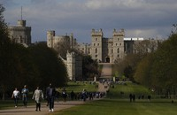 People walk along the Long Walk in front of Windsor Castle in Windsor, England, on April 16, 2021. (AP Photo/Alastair Grant)