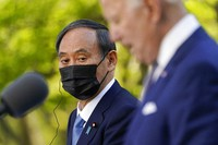 Japanese Prime Minister Yoshihide Suga, listens as President Joe Biden speaks at a news conference in the Rose Garden of the White House, Friday, April 16, 2021, in Washington. (AP Photo/Andrew Harnik)