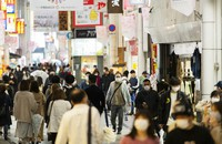 People wearing face masks walk through a shopping street in the famed Namba district of Osaka, western Japan, Saturday, April 17, 2021. (AP Photo/Hiro Komae)