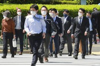 People wearing face masks to protect against the spread of the coronavirus walk across a pedestrian crossing in Tokyo, Monday, April 19, 2021. (AP Photo/Koji Sasahara)