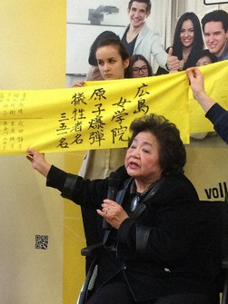 "Setsuko Thurlow gives testimony as she spreads a cloth with the names of students from her alma mater Hiroshima Jogakuin Girls' High School who passed away in the atomic bombing, at the school in this image taken from the film ""The Vow from Hiroshima."""