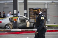 A police commander walks by as police investigate a crime scene where Jontae Adams, 28, and his daughter Jaslyn, 7, were shot, resulting in Jaslyn's death at a McDonald's drive-thru at the corner of W. Roosevelt Road and South Kedzie Avenue on April 18, 2021, in Chicago. (Anthony Vazquez/Chicago Sun-Times via AP)