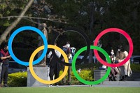 In this March 19, 2021, file photo, people take pictures of the Olympic rings installed by the Japan Olympic Museum in Tokyo. (AP Photo/Hiro Komae, File)