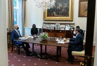 In this photo posted on U.S. President Joe Biden's Twitter account, Japanese Prime Minister Yoshihide Suga, right, and President Biden are seen sitting for a meeting at the White House in Washington on April 16, 2021. Burgers can be seen served on the table.