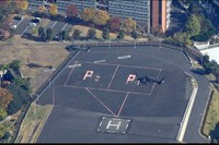 """Two U.S. Army Black Hawk helicopters are seen taking off from a parking space marked with a """"P,"""" which is near a university ground, upper left, and apartment buildings, in the Roppongi heliport in Tokyo at around noon on Nov. 17, 2020. At heliports in Japan, helicopters are required to depart and land in zones indicated with an """"H,"""" for safety. (Mainichi/Koichiro Tezuka)"""