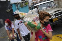 Young people carry bags of basic food staples, such as pasta, sugar, flour and kitchen oil, provided by a government food assistance program, for delivery in the Santa Rosalia neighborhood of Caracas, Venezuela, on April 10, 2021. (AP Photo/Matias Delacroix)