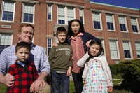 John Horrigan, top left, and his wife Kim Horrigan, top right, stand for a photograph with their children, from the left, William, 3, Conor, 8, and Sofia, 4, all of Quincy, Mass., outside Montclair Elementary School, in Quincy, on April 13, 2021. (AP Photo/Steven Senne)