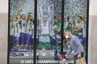 A man and a young boy walk past a Real Madrid poster of the team celebrating in a merchandising shop in Madrid, Spain, on April 19, 2021. (AP Photo/Paul White)