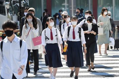 強い日差しで気温が上昇する中、袖をまくって歩く人たち=福岡市博多区で2021年4月21日午後2時33分、津村豊和撮影