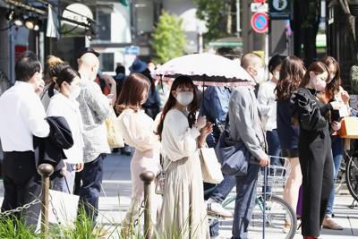 強い日差しの中、信号待ちする歩行者たち=東京都中央区で2021年4月21日午後2時14分、小出洋平撮影