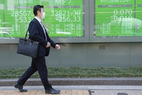 A man walks by an electronic stock board of a securities firm in Tokyo on April 21, 2021. (AP Photo/Koji Sasahara)