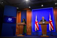 Britain's Prime Minister Boris Johnson, right, gives a press conference flanked by Nikki Kanani, medical director of primary care for NHS England and NHS improvement, at 10 Downing Street, amid the coronavirus disease outbreak, in London, on April 20, 2021. (Toby Melville/Pool via AP)