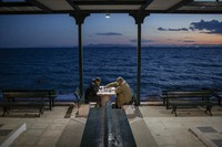 Two men wearing protective face masks play chess in Alimos, a seaside suburb of Athens, on April 20, 2021. (AP Photo/Petros Giannakouris)
