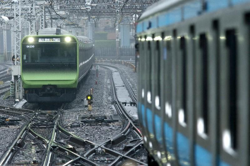 京浜東北線のE233系(右)を追うように走る山手線のE235系。首都圏では通勤電車同士のコラボが頻繁に見られる=東京都の浜松町-田町間で2021年4月、金盛正樹撮影