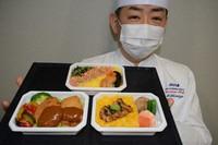 Makoto Shimizu, executive western cuisine chef at ANA Catering Service Co., shows some in-flight meals sold online. (Mainichi/Tadakazu Nakamura)