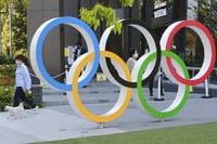 A woman with her dog walks past the Olympic rings in Tokyo, on April 20, 2021. (AP Photo/Koji Sasahara)