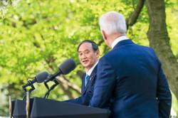 首脳会談後、バイデン米大統領との共同会見に臨む菅義偉首相(左)(2021年4月16日、ワシントンのホワイトハウスで) (Bloomberg)