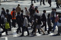 People wearing protective masks to help curb the spread of the coronavirus walk along a pedestrian crossing on April 21, 2021, (AP Photo/Eugene Hoshiko)