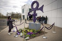 A fan takes a photo of a memorial, on April 21, 2021, as others line up to go into Paisley Park in Chanhassen, Minn., on the fifth anniversary of Prince's death. (AP Photo/Stacy Bengs)