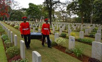 In this Nov. 13, 2016 file photo, two members of Kenya's Military Police walk past graves as they leave after attending a Remembrance Sunday event, to honor the contribution of those British and Commonwealth military who died in the two World Wars and later conflicts, at the Nairobi War Cemetery in Kenya. (AP Photo/Ben Curtis)