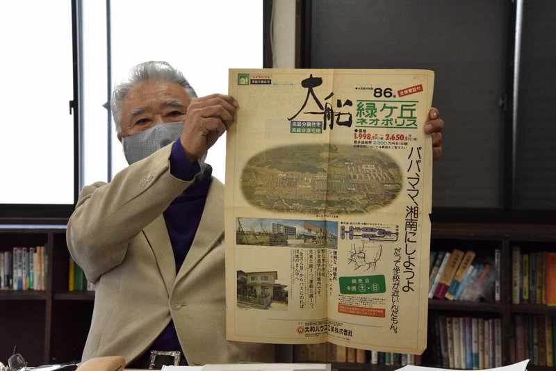 売り出し当時の広告を広げてみせる吉井信幸さん=横浜市で、筆者撮影