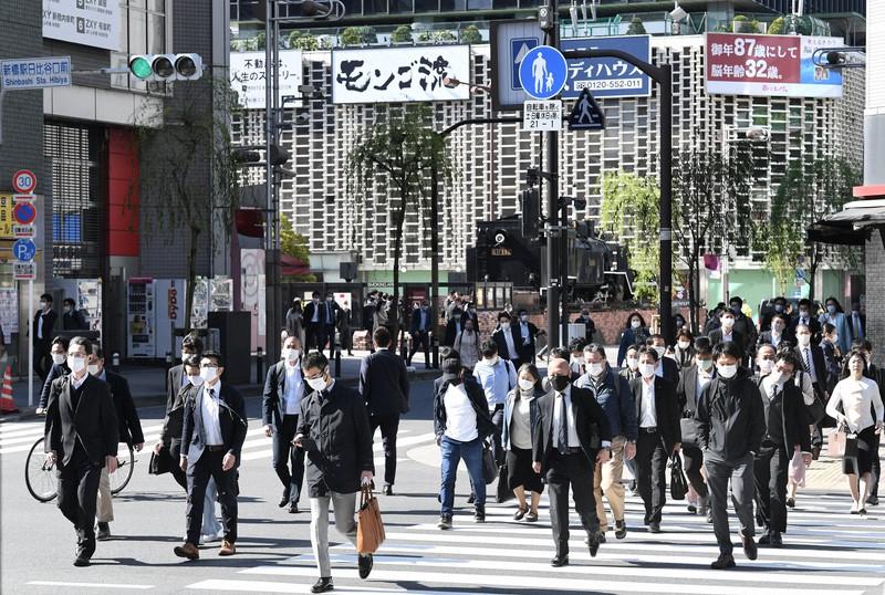 3度目の緊急事態宣言適用後、初の平日の朝にマスク姿で通勤する大勢の人たち。奥は新橋駅前のSL広場=東京都港区で2021年4月26日午前8時10分、竹内紀臣撮影