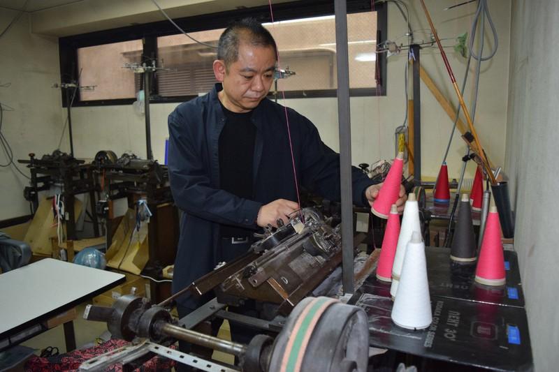 ニット編み機を調整する小高集さん=清水憲司撮影
