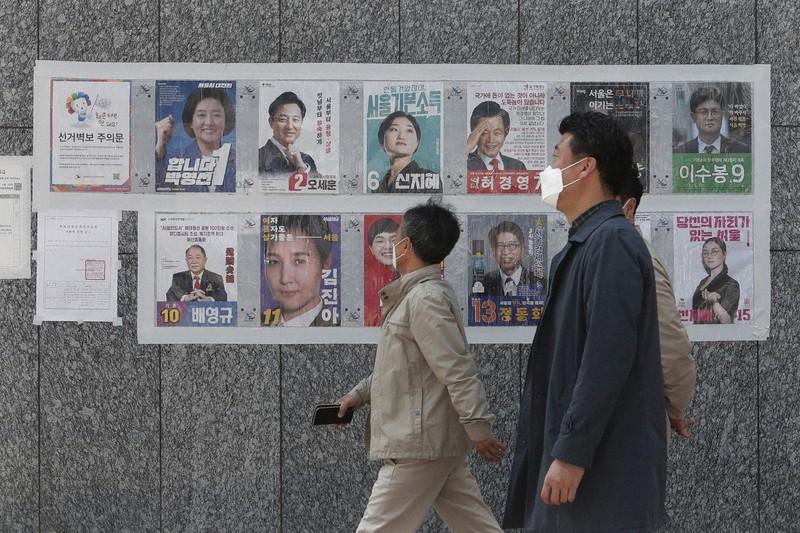 選挙ポスターの掲示板の前を歩く人々=ソウルで2021年4月7日、AP