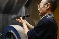 Yutaka Yazaki is seen examining a knife sharpened on a rotating whetstone at the edged tool shop Ubukeya in Tokyo's Chuo Ward on March 31, 2021. (Mainichi/Emi Naito)
