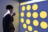 Images are seen projected on the wall of conference room Ricoh Prism, after someone spoke into a cube-shaped controller, in Tokyo's Ota Ward on April 15, 2021. (Mainichi/Takehiko Onishi)