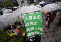 "Participants in a rally are seen protesting a planned draft revision to the Immigration Control and Refugee Recognition Act in Osaka's Kita Ward, on May 5, 2021. The sign reads, ""The revision to the immigration law is a violation of the International Bill of Human Rights."" (Mainichi/Rei Kubo)"