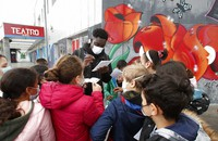 Actor Giuseppe Dave Seke signs autographs to children, in Milan, Italy, on April 27, 2021. (AP Photo/Antonio Calanni)