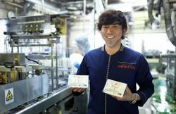 できたての豆腐を手にする染野屋の小野篤人社長=茨城県取手市で小川昌宏撮影