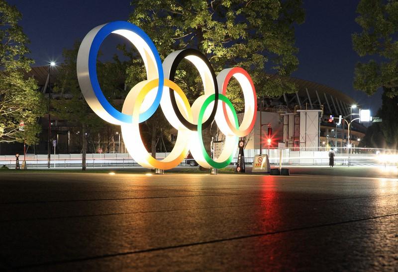 Tanda Olimpiade yang menyala.  Stadion nasional di belakang tetap dalam kegelapan malam = Diambil langsung oleh Umemura pada tanggal 18 Januari 2021 di Shinjuku-ku, Tokyo.