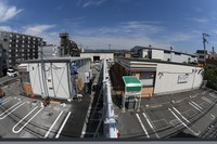 The two 7-Eleven stores at the Higashiosaka Minamikamikosaka 7-Eleven branch are seen in this image taken with a fish-eye lens in Higashiosaka, Osaka Prefecture, on April 27, 2021. On the left is the temporary structure built in the parking lot by Seven Eleven Japan Co., and on the right is the previously existing shop. (Mainichi/Daiki Takikawa)