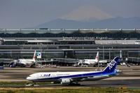 Planes are parked at gates at Tokyo's Haneda airport as Mount Fuji appears on May 4, 2021. (AP Photo/Kiichiro Sato)